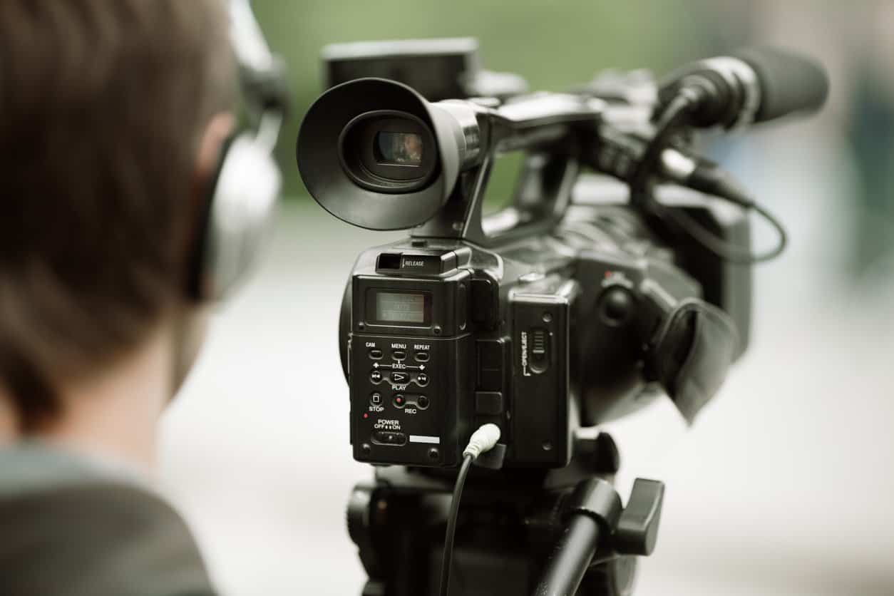 professional camcorder on the tripod, selective focus on nearest part