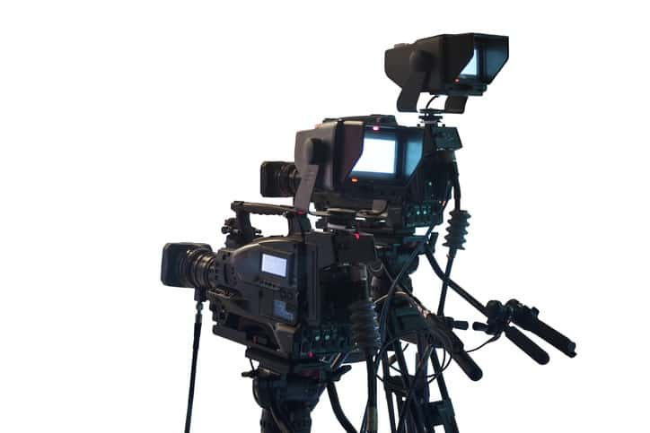 DSLR video camera mounted on a tripod with follow focus and matte box on white background